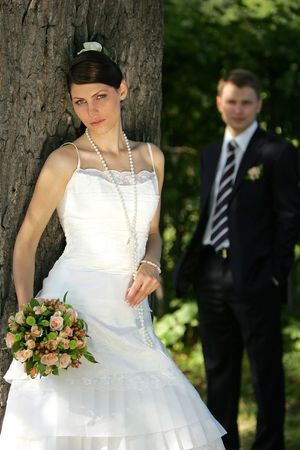 Close up of young bride in forest with groom in background. photo