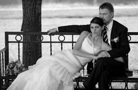 Close up of newlywed couple sat on park bench in countryside. photo