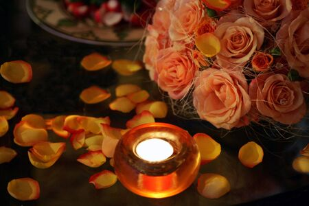 Background of burning tea light candles, bouquet of flowers and rose petals.