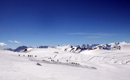 mixed age range: Skiers on snowy mountainside under blue sky, Switzerland. Stock Photo
