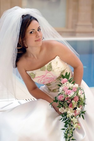 Smiling young bride in traditional white wedding dress with veil, swimming pool in background. photo