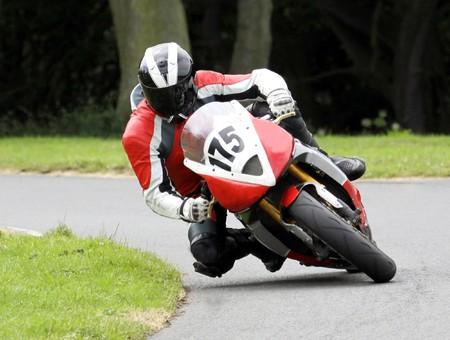 motociclista: Adulto equitazione moto veloce intorno angolo sulla pista.