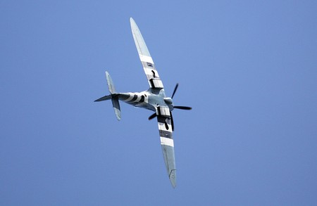 Retro spitfire aircraft in acrobatic flight with blue sky background. photo