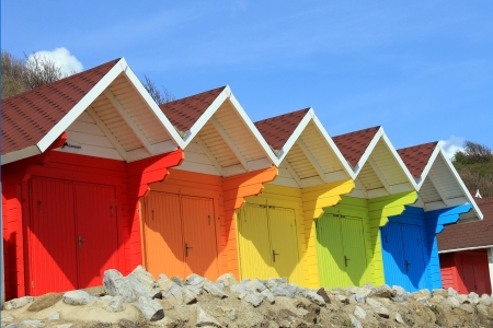 Row of colorful beach huts or chalets with blue sky background and copy space. Stock Photo