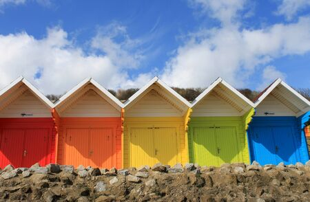Row of colorful beach chalets with blue sky and cloudscape background, summer scene. photo