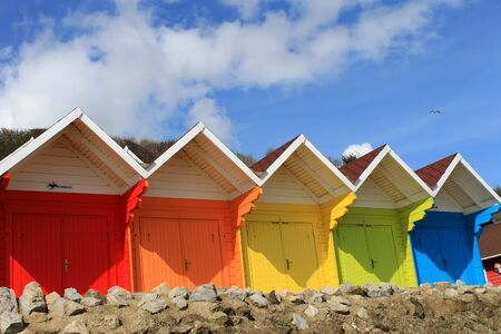 Row of colorful beach huts with blue sky and cloudscape background, summer beach scene. photo