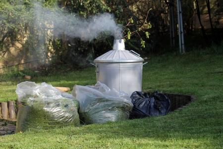 inceneritore: Garden inceneritore accanto a sacchi di erba tagliata, prato in primo piano.