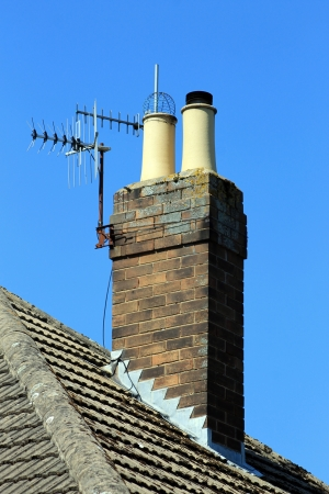 flue season: Chimney on tiled roof with aerial, blue sky background.