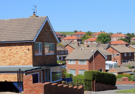 architecture detached house: English housing estate with blue sky background.