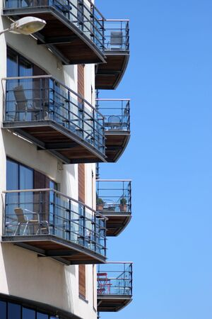 veranda: Holiday apartments in tower block with blue sky background.