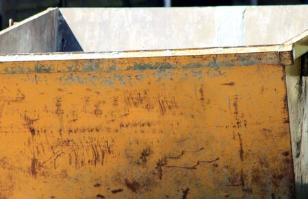 skip: Front of old empty yellow refuse skip outdoors.