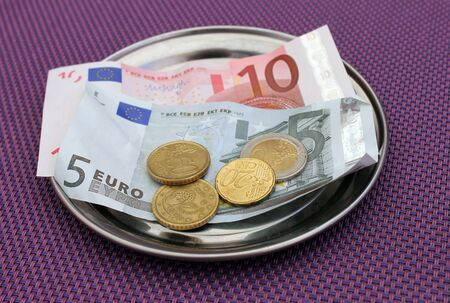 denominational: Euro tipsand payment for bill on on restaurant table.