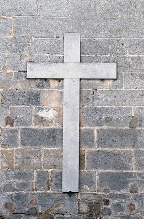 piety: Old marble religious cross on gray or grey wall.