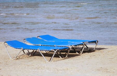 loungers: Sun loungers or beds on sandy beach, summer holiday scene.