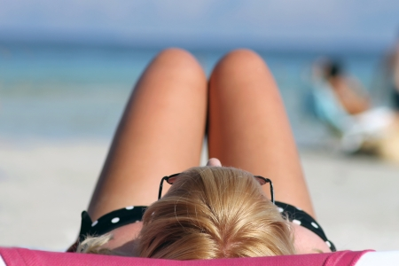 sunbathing: Teenage girl sunbathing on beach with sea in background and copy space, focus on head, blond hair and sunglasses.