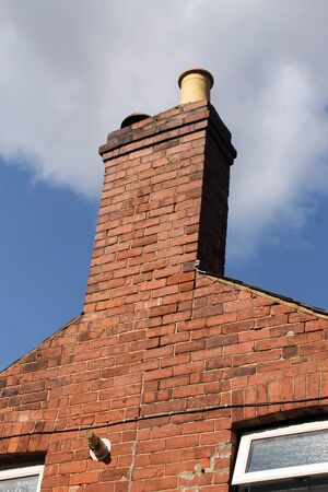 typically english: Chimney of old brick house or home with blue sky and cloudscape background.