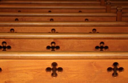 pews: Row of wooden pews receding in church
