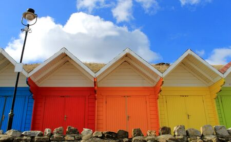 Row of colorful beach chalets with blue sky background. photo