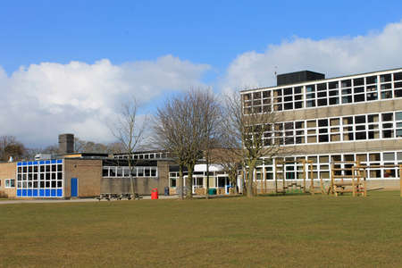 secondary school: Exterior of modern school building with playing field in foreground. Stock Photo
