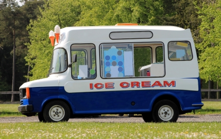 cream and green: Side view of ice cream van in green countryside Stock Photo