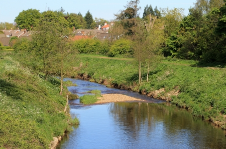 meandering: Scenic view of meandering river with village houses in background. Stock Photo