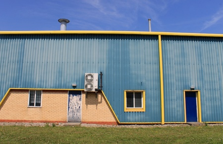 warehouse building: Exterior of blue and yellow warehouse building with air conditioning.