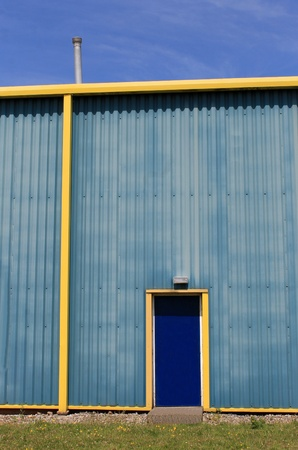 warehouse building: Exterior of blue and yellow modern warehouse building, sky background.