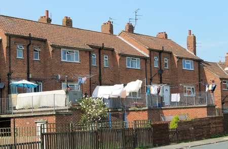 terraced: Rear view of modern terrace houses with washing drying in back yard.