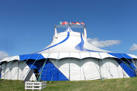 big top: Blue and white big top circus tent in field with flags from around World. Stock Photo
