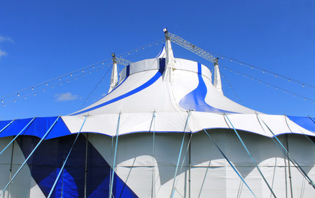 big top: Blue and white big top circus tent with sky background.