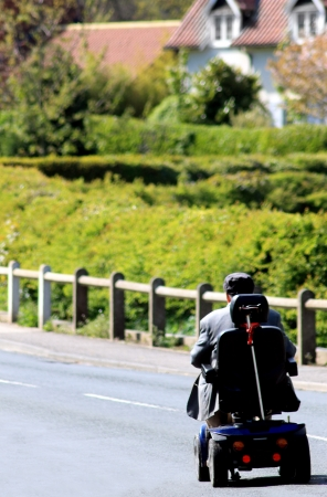 Rear view or senior man riding mobility scooter on countryside road. photo