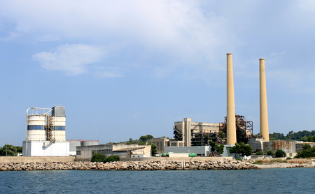 tall chimney: Industrial factory with tall chimney view from ocean. Stock Photo