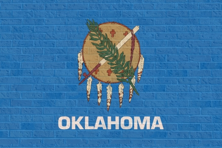 oklahoma: Oklahoma state flag of America on brick wall, isolated on white background.