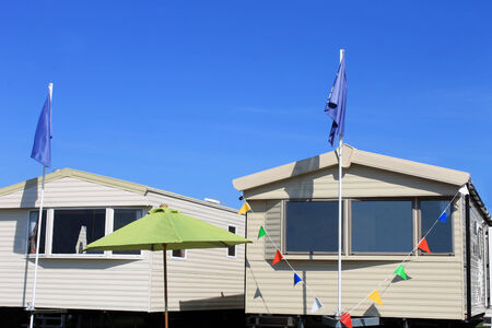 Exterior of two new caravans on trailer park with blue sky background. photo