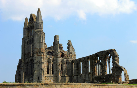 whitby: Scenic view of the ruins of Whitby Abbey with blue sky and cloudscape background.
