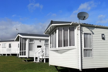 Scenic view of a caravan or trailer park in summer with blue sky and cloudscape background. Archivio Fotografico