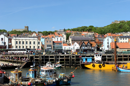 particularly: SCARBOROUGH, NORTH YORKSHIRE, ENGLAND - 19th May 2014: Scarborough town and harbor seaside resort on the 19th of May 2014. This is a popular tourist destination every summer, particularly from visitors from European countries. Editorial