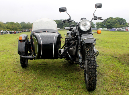 sidecar: Motorbike and sidecar in a countryside field.