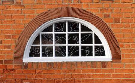architectural exteriors: Exterior of a brick building with an arched window. Stock Photo