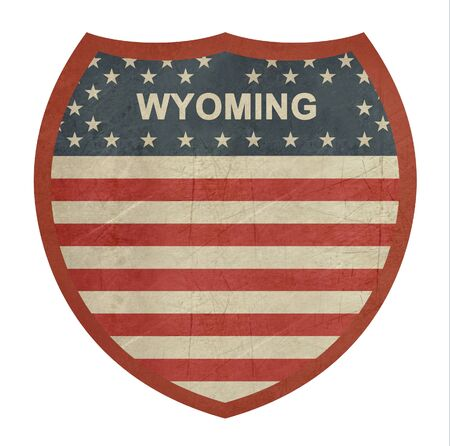 roadtrip: Grunge Wyoming American interstate highway sign isolated on a white background.