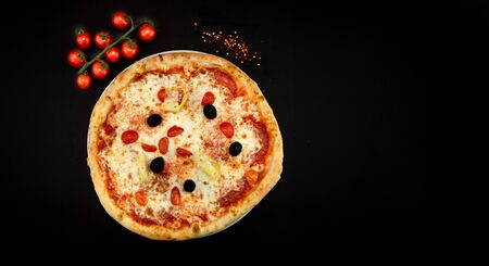 Isolated round pizza on black background with tomatoes aside. Space for text and enlargement. Italian style recepies and authentic fresh ingredients.