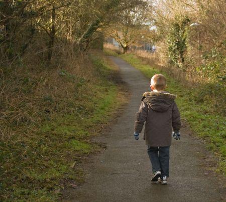walking down: young boy in a winter coat walking away down a path Stock Photo