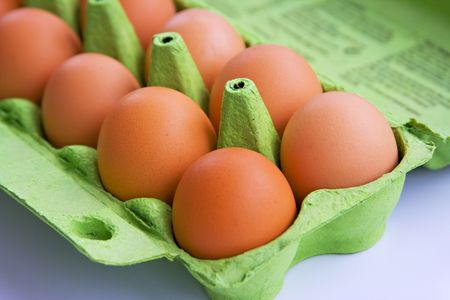 Brown eggs stored in a green cardboard carton