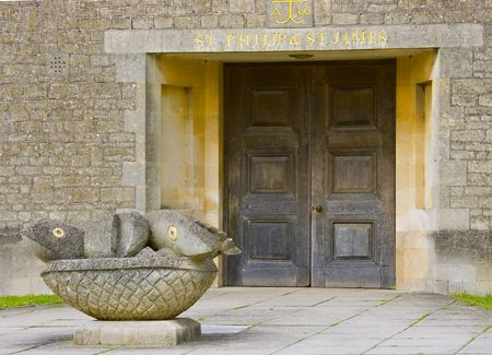 Church doorway with a statue of the loaves and fishes outside Stock Photo - 4888308