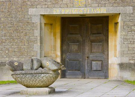 pez cristiano: Puerta de la iglesia con una estatua de los panes y los peces fuera Foto de archivo