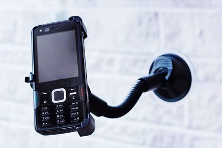 Mobile phone in hands free holder Stock Photo
