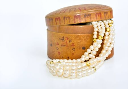 tooled: Simulated pearl beads spilling out of a tooled leather pot Stock Photo