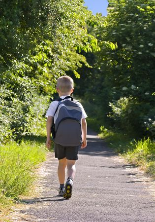 for kids: Young boy wearing a backpack ready for school Stock Photo