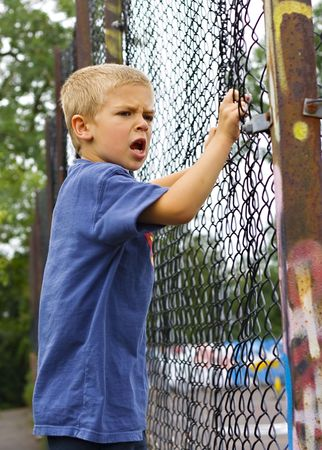 An angry young boy shouting through a chain link fence