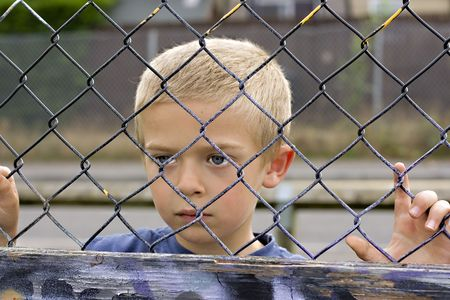 A portrait of a young boy looking through a chain link fence Standard-Bild